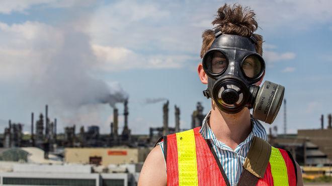 Un jeune homme portant à masque à gaz avec en arrière plan une usine de traitement de sables bitumneux au Canada