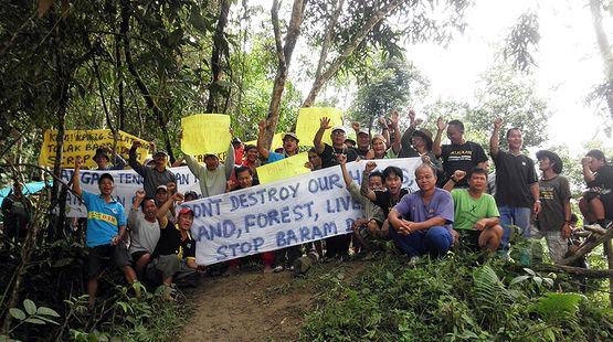 Des autochtones posent avec leurs pancartes dans la forêt tropicale du Sarawak pour manifester contre le barrage de Baram.