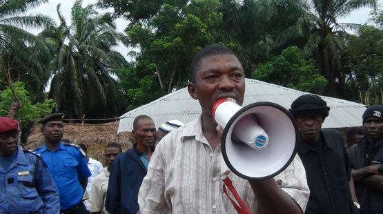 Surveillé par des militaires, l'ancien parlementaire de la Sierra Léone Hon. Musa Sama, parle dans un mégaphone dans une plantation de palmiers à huile
