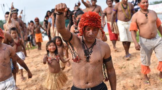 Les Mundurucús manifestent. Au premier plan, un Indien tatoué le point levé.