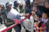 Un policier, protégé par son grand bouclier et son casque à visière, lève sa matraque contre une femme main dans la main avec une enfant au regard terrorisé qui tient un bouquet de fleurs