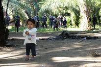 Petite fille effrayée (au premier plan) par les paramilitaires armés (à l'arrière plan)